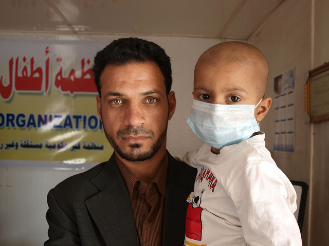 Un padre sostiene a su hijo enfermo de cáncer en Basora, poco después de la muerte de otra hija por la misma enfermedad. La foto se tomó en febrero de 2011. El niño falleció unos meses más tarde. Crédito: Karlos Zurutuza/IPS.