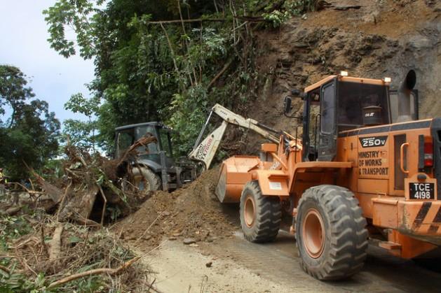 Obreros despejan una carretera bloqueada por un deslizamiento de tierras en Trinidad. Las indemnizaciones por daños y pérdidas a causa del cambio climático se ha vuelto una importante demanda de los países en desarrollo. Crédito: Desmond Brown/IPS.