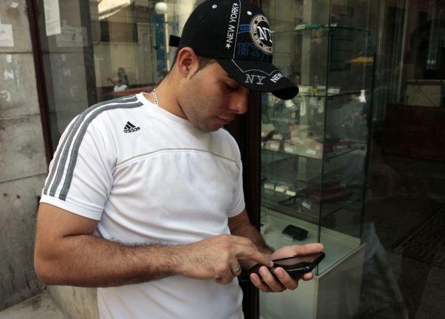 Un joven cubano, luciendo un gorro con inscripciones de Nueva York y una camiseta de la marca Adidas, consulta su teléfono celular en La Habana. Crédito: Jorge Luis Baños/IPS