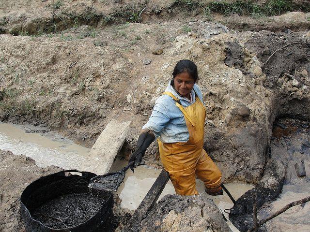 La quichua Rosa Tanguila limpia la contaminación petrolera que dejó Texaco en un arroyo de su comunidad, Rumipamba, en la Amazonia ecuatoriana. Crédito: Gonzalo Ortiz/IPS