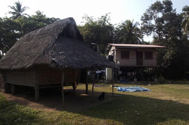 """Una rara combinación de choza tradicional y construcción de material en la isla de Nicobarese. Una familia mantuvo su vivienda junto a un """"refugio permanente"""" de concreto otorgado por el gobierno como ayuda tras el tsunami de 2004. Crédito: Malini Shankar/IPS."""