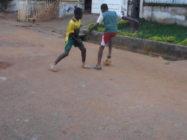 Niños de un barrio pobre de Yaundé, la capital de Camerún, juegan al fútbol. Están entusiasmados por el comienzo de la Copa Mundial de la FIFA, a la Camerún se clasificó siete veces, un récord africano. Crédito: Cortesía de Ngala Killian Chimtom