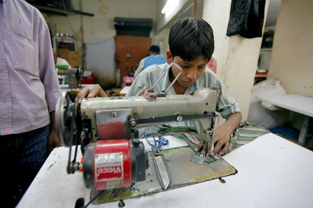 Un niño trabaja en una fábrica textil en India. Crédito: Photo Stock