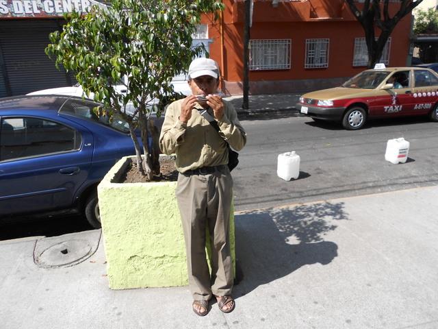 Leobardo Gómez, de 44 años, trata de sobrevivir tocando la armónica por las calles de Ciudad de México, porque las secuelas de un accidente no le permiten realizar su oficio de albañil. Crédito: Emilio Godoy/IPS