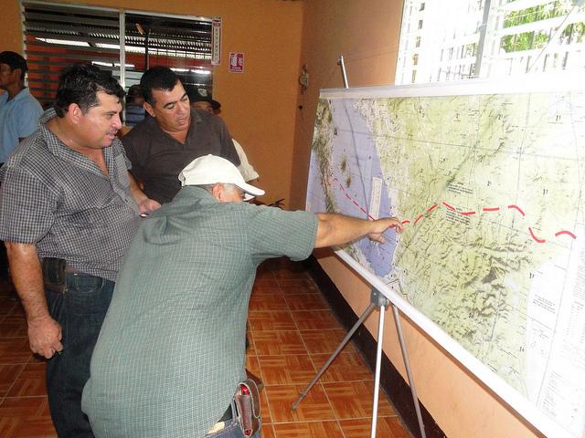Tres agricultores analizan el trazado del Gran Canal Interoceánico sobre el mapa de Nicaragua, que la empresa china HKND Group presentó en la sureña ciudad de Rivas, durante un encuentro con afectados por la gigantesca obra. Crédito: José Adán Silva/IPS
