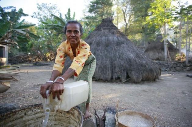Una mujer de Pune, en Timor Oriental, recoge agua para su casa. Un informe de la ONU destaca mayor acceso a fuentes de agua potable, mejora en las condiciones de vida de los habitantes de tugurios y paridad de género alcanzada en la enseñanza primaria. Crédito: UN Photo/Martine Perret