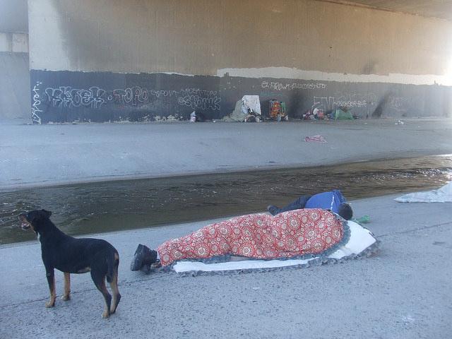 Un deportado desde Estados Unidos duerme arrebujado bajo el puente fronterizo sobre el río Tijuana, en El Bordo, en la esquina más al norte de México, al lado de la frontera. Crédito: Daniela Pastrana /IPS