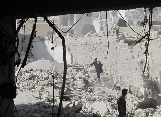Un miembro del equipo de defensa civil de Alepo busca sobrevivientes tras el ataque aéreo con una bomba de barril en la ciudad siria en agosto de 2014. Crédito: Shelly Kittleson/IPS.
