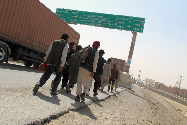 Migrantes afganos caminan por el arcén, tras volver deportados desde Irán, en el puesto fronterizo de Zaranj, en la remota provincia de Nimroz. Crédito: Karlos Zurutuza/IPS