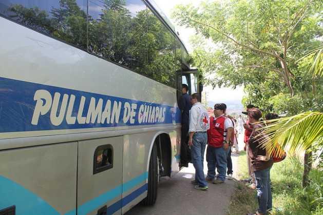 Voluntarios de la Cruz Roja abordan un autobús donde llegan niños y niñas migrantes en el puesto fronterizo hondureño de Corinto, para supervisar su estado y entregarles una bolsa de ayuda solidaria. Crédito: Thelma Mejía/IPS