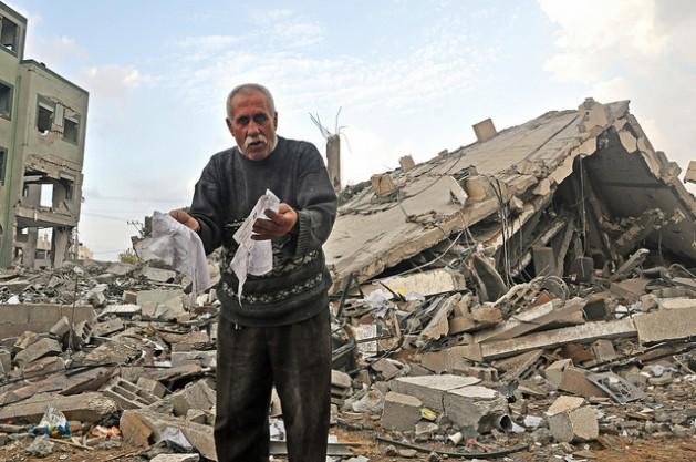 Abu Mohammed, cuya familia perdió su casa tras un bombardeo de Israel, desentierra papeles entre los escombros de un edificio de oficinas del gobierno en Gaza. Crédito: Eva Bartlett/IPS