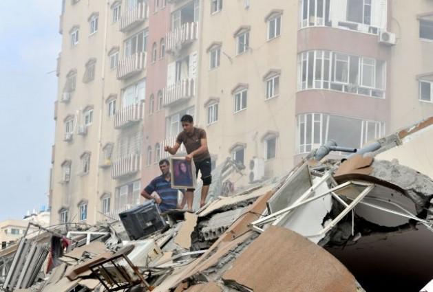 Palestinos buscan sus pertenencias entre los escombros de un edificio de apartamentos de Gaza que un ataque aéreo israelí destruyó el 24 de agosto. Crédito: Foto de la ONU/Shareef Sarhan