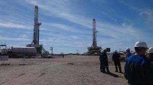 Unos técnicos dialogan sobre su actividad entre dos torres de perforación en el yacimiento de Loma Campana, en Vaca Muerta, en Argentina. Crédito: Fabiana Frayssinet/IPS