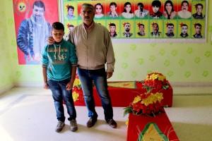 Ali Jalil y su hijo Diar posan en la Asociación para los Mártires de Serekaniye, en la zona kurda de Siria, junto a dos ataúdes que acaban de preparar para muertos en combates con los extremistas yihadistas del Estado Islámico. Crédito: Karlos Zurutuza/IPS
