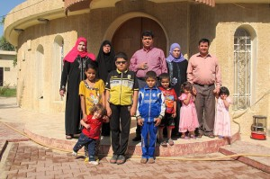 La familia Ismam, de desplazados mandeos que huyen del grupo extremista Estado Islámico, posa en la entrada del Consejo Mandeo de la ciudad iraquí de Kirkuk, donde están acogidos temporalmente. Crédito: Karlos Zurutuza/IPS