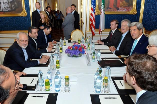 Con las banderas de ambos países lado a lado, el secretario de Estado estadounidense, John Kerry, se sienta frente al ministro de Relaciones Exteriores iraní, Mohammad Javad Zarif, el 13 de julio de 2014 en Viena, previo al inicio de una reunión bilateral centrada en el programa nuclear de Teherán. Crédito: Departamento de Estado