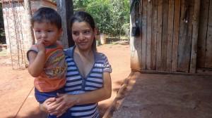 Soledad Olivera con su hijo en brazos, delante de su nuevo cuarto de baño, con inodoro y agua corriente, que reemplazó a una precaria letrina en su vivienda en un caserío de Bonpland, en la norteña provincia argentina de Misiones. Crédito: Fabiana Frayssinet/IPS