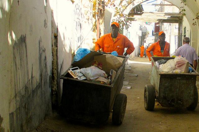 Dos barrenderos de origen subsahariano acarrean sus carros de basura en la Ciudad Vieja de Trípoli, la capital de Libia. Crédito: Karlos Zurutuza/IPS