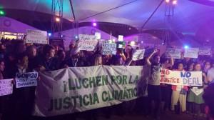 Mientras los gobiernos de 195 países aprobaban el documento final de la COP 20, en Lima la madrugada del 14 de diciembre, los activista protestaban ya por los débiles resultados de las negociaciones climáticas, a las afueras del salón Cusco de la plenaria, donde se pactó el acuerdo. Crédito: Diego Arguedas Ortiz/IPS