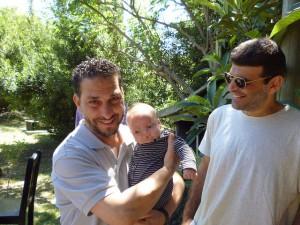 Los seis liberados del centro de detención estadounidense de Guantánamo hicieron fila para cargar a este bebé uruguayo. En la imagen, el tunecino Abdul Bin Mohammed Abis Ourgy aupa al pequeño, y el sirio Ali Hussein Muhammed Shaaban los observa. Crédito: Diana Cariboni/IPS