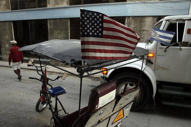 Las banderas de Estados Unidos y de Cuba adornan un bicitaxi en La Habana, horas después del anuncio del restablecimiento de relaciones diplomáticas entre los dos países, rotas en enero de 1961. Crédito: Jorge Luis Baños/IPS