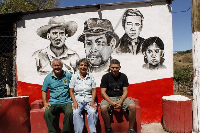 Los esposos Florentino Menjívar (izquierda) y María Dolores Gómez, junto a Víctor Manuel Escalante, al pie del mural que destaca a figuras de la guerra civil, en la comunidad Dimas Rodríguez, un asentamiento de antiguos guerrilleros en el municipio de El Paisnal, que apuesta al turismo rural. Crédito: Edgardo Ayala/IPS