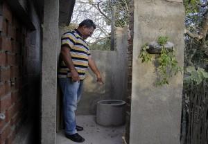El pastor Demas Rodríguez muestra una letrina seca abonera instalada en el pueblo de Babiney, en la provincia de Granma, en el oriente de Cuba. Crédito: Jorge Luis Baños/IPS
