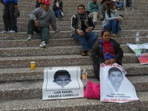 La náhuatl Metonia Carrillo mantiene asida una pancarta con la foto de su hijo Luís Ángel Abarca, uno de los 43 estudiantes desaparecidos el 26 de septiembre en Iguala, mientras descansa en las gradas del Auditorio Nacional durante una protesta de familiares en la capital mexicana, al cumplirse cuatro meses de su secuestro. Crédito: Emilio Godoy /IPS