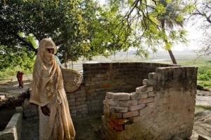 """Una mujer dalit junto al baño de una casa de casta alta en la localidad india de Mainpuri, donde se produjeron actos de violencia contra quienes intentan abandonar la profesión de """"recolectores manuales"""". Crédito: Shai Venkatraman/IPS"""