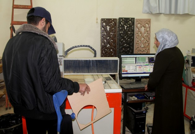 Samah Shaheen (a la derecha), una joven discapacitada de Gaza que aprende talla en madera por computadora en el programa Irada. Crédito: Khaled Alashqar/IPS