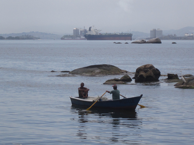 Pescadores salen con su pequeño barco en la bahía de Guanabara, desde una playa en Isla del Gobernador. Al fondo una isla con depósitos de hidrocarburos de Petrobrás, la estatal brasileña, y un buque petrolero. Crédito: Mario Osava/IPS.