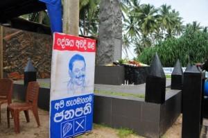Un cartel electoral del actual presidente de Sri Lanka, Mahinda Rajapaksa, se encuentra junto a un monumento recordatorio del tsunami que asoló la ciudad austral de Peraliya. Crédito: Amantha Perera/IPS