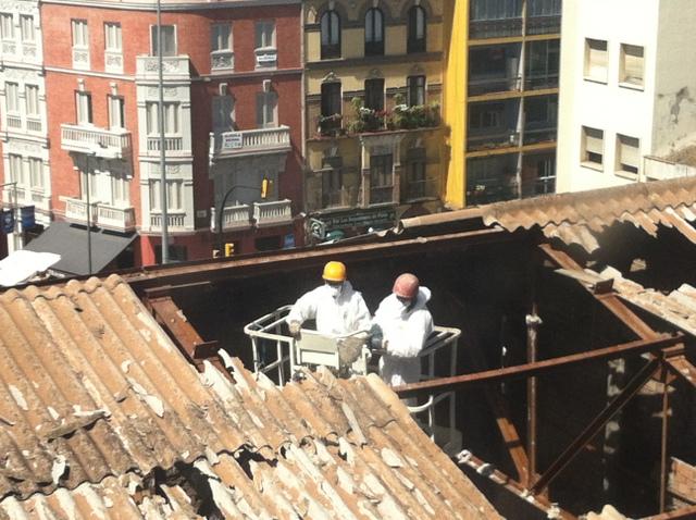 Dos operarios trabajan en la eliminación del amianto en el techo de un edificio que albergó unos cines en el centro de la sureña ciudad española de Málaga, en mayo de 2014. Crédito: Cortesía de la Plataforma Málaga Amianto Cero