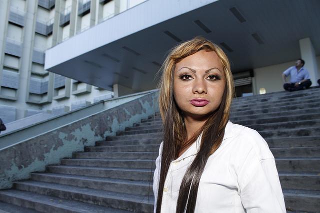 Daniela Alfaro, estudiante de educación para la salud, en la entrada de la Facultad de Medicina de la Universidad de El Salvador. Esta joven trans ha denunciado sin éxito las agresiones y el acoso de que es víctima en el centro de la capital del país. Crédito: Edgardo Ayala/IPS