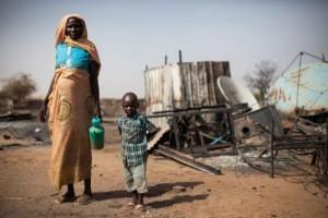 Una madre y su hijo junto a los restos quemados de su casa en Khor Abeche, en el sur de Darfur, en abril de 2014. Crédito: Foto de la ONU / Albert González Farran