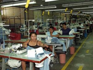 Trabajadoras confeccionan ropa deportiva de una marca estadounidense en una maquila de la Zona Franca de San Bartolo, en el municipio de Ilopango, en el este de El Salvador. En la planta trabajan 350 personas por cada turno de ocho horas, 80 por ciento mujeres, que ganan el salario mínimo. Crédito: Edgar Romero/IPS