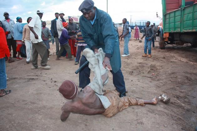 Un policía intenta levantar del suelo a un joven alcoholizado en la ciudad de Nyeri, en Kenia. Crédito: Miriam Gathigah/IPS