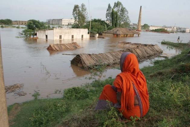 Una mujer observa impotente cómo el agua inunda su vivienda con techo de paja y todas sus posesiones a las afueras de la ciudad de Bhubaneswar, en el oriental estado de Odisha, en India, en 2008. Crédito: Manipadma Jena/IPS