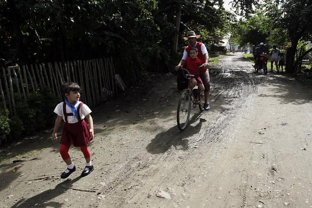 Niños y otros viandantes transitan por una calle secundaria del municipio Jesús Menéndez, en el oriente de Cuba. Mejorar la vialidad es uno de los objetivos de la mayor autonomía de los poderes municipales. Crédito: Jorge Luis Baños/IPS