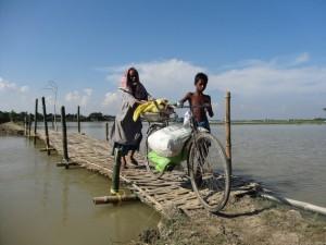 Las devastadoras inundaciones que en 2014 causaron estragos en el nororiental estado de Assam, en India, llevaron al gobierno a construir puentes de bambú. Este hombre y este niño van de una aldea a otra en barco y cruzan los puentes a pie. Crédito: Priyanka Borpujari/IPS