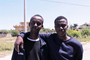 Mohamed (izquierda) y Ahmed, dos inmigrantes somalíes que sobrevivieron el cruce del Mediterráneo y ahora están alojados en uno de los centros de primeros auxilios y recepción de Siracusa, en el sur de Italia. Crédito: Silvia Giannelli / IPS