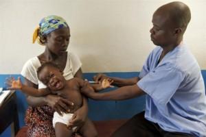 Un bebé recibe la vacuna contra el sarampión de manos del vacunador Joseph Kamara, en la clínica comunitaria de Tagweh, Liberia. Crédito: Unicef