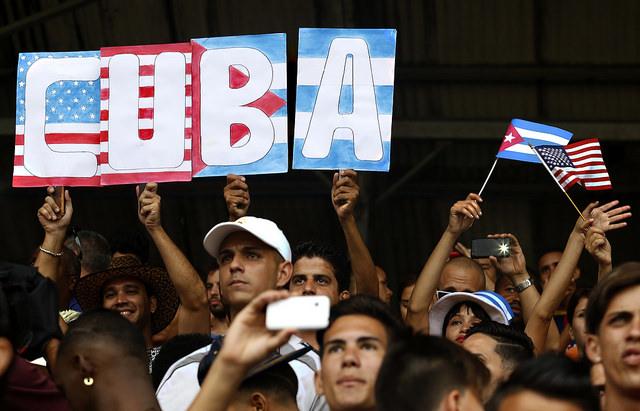 Aficionados con un cartel con las banderas de Cuba y Estados Unidos, durante un partido amistoso de fútbol en La Habana, entre un equipo del país anfitrión y el club Cosmos de Nueva York, el 2 de junio . Este ha sido el primer encuentro deportivo entre equipos de los dos países, tras el inicio del deshielo bilateral, en diciembre. Crédito: Jorge Luis Baños /IPS