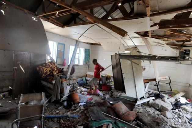 Un estudiante palestino revisa los daños sufridos por una escuela de la ONU en el campamento de refugiados de Jabalia, en el norte del territorio palestino de Gaza, bombardeada por Israel el 30 de julio de 2014. Crédito: UN Photo/Shareef Sarhan.