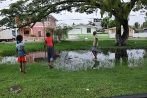 Niños pescando en una hondonada en su barrio de Guyana. Crédito: Desmond Brown/IPS.