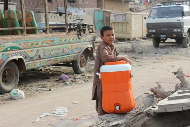 Un niño de un asentamiento informal en Karachi carga con un recipiente para recoger agua en los grifos de viviendas particulares, que los habitantes más pudientes ponen a disposición de los pobres como un acto de caridad. Crédito: Zofeen T. Ebrahim/IPS