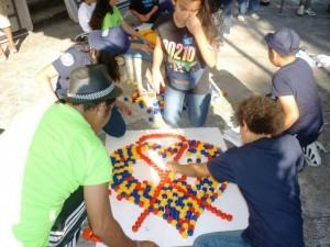 Unos adolescentes crean con tapones el lazo que simboliza la lucha contra el sida, en una de las actividades que se repiten en América Latina para concienciar a la población sobre la enfermedad. Crédito: Onusida América Latina