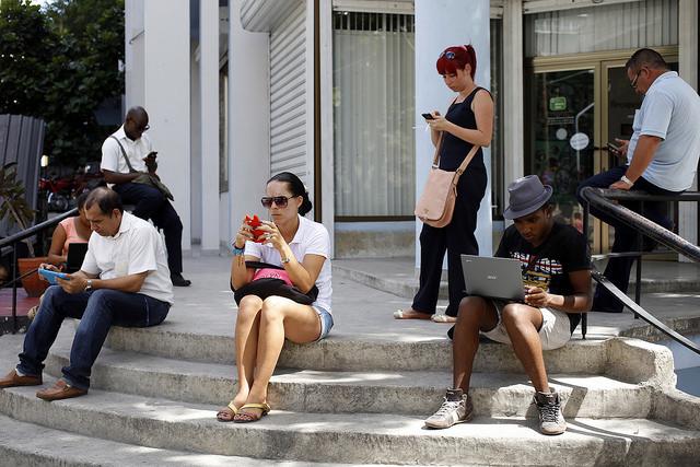 Un grupo de personas en el exterior de la biblioteca médica ubicada en una céntrica calle de El Vedado, en La Habana, donde se puede acceder a Internet por una red inalámbrica. Esta es una de las 35 redes de este tipo instaladas por la estatal Empresa de Telecomunicaciones en el país. Crédito: Jorge Luis Baños/IPS