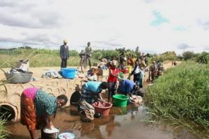 Lugareños de Mchinji, en Malawi, lavan ropa en un arroyo. Crédito: Claire Ngozo/IPS