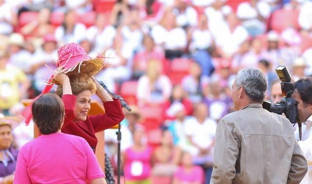 La presidenta Dilma Rousseff mientras se pone un sombrero de trabajadora rural, que le regalaron el 13 de agosto en Brasilia, en la clausura de una marcha nacional de mujeres del campo. Mantener sobre su cabeza la jefatura del Estado es una tarea que se complica día a día para la mandataria brasileña. Crédito: Lula Marques/ Agência PT